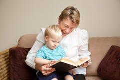 Großmutter oder Kindermädchen, die zu einem Kind lesen Stockfotografie