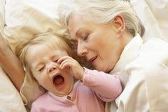 Großmutter-Umarmungsenkelin im Bett Stockbild