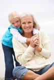 Großmutter und Enkelin, die auf Strand sitzen Stockbild