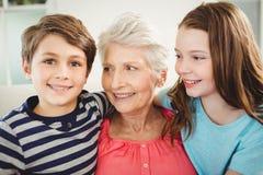 Großmutter und Enkelkinder, die zusammen auf Sofa sitzen Lizenzfreie Stockfotos