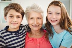 Großmutter und Enkelkinder, die zusammen auf Sofa sitzen Lizenzfreies Stockbild
