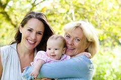 Großmutter und Mutter, die mit Baby lächeln Stockbilder