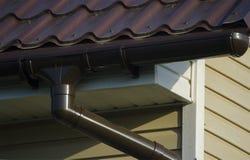 Grondaia sul tetto della casa Colore del Brown fotografie stock