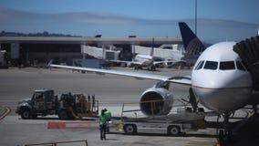 Grondbemanning die bij het leegmaken van een vliegtuig werken stock video