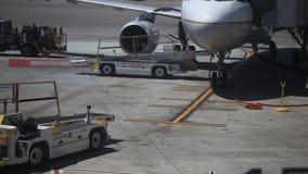 Grondbemanning die bij het leegmaken van een vliegtuig werken stock videobeelden