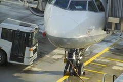 Grondbemanning die en onder een passagiersvliegtuig bijtanken werken Royalty-vrije Stock Foto