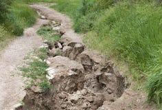 Gronderosie na zware regen op een bergweg stock afbeeldingen