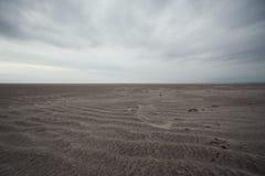 Grondmening van zandig strand op bewolkte dag stock foto's