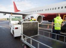 Grondpersoneel die door Vliegtuig en Vrachtwagen aan Baan werken royalty-vrije stock afbeelding
