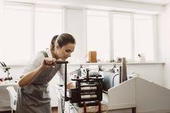 Grondstoffenverwerking Vrouwelijk vrouwengoudsmid het bewerken metaal op ambacht rollende machine stock foto's