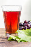 Gronowy sok i grono winogrona z zielonymi liśćmi Zdjęcie Stock