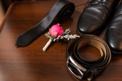 Groom's accessories: flower boutonniere in focus, leather belt, necktie, shoes. Royalty Free Stock Photo