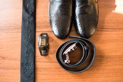 Groom's accessories: leather belt, black shoes and a watch in focus, necktie. Details Stock Image