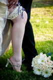 Groom's hand on bride's leg with blue garter Stock Photos