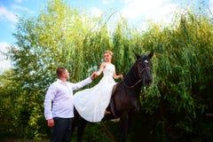 Groom водит лошадь уздечкой Невеста сидит в saddl стоковое фото rf