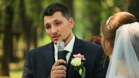 Groom говорит присягу на свадебной церемонии стоя в украшенном своде сток-видео