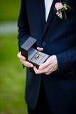 Groom держа обручальные кольца Стоковое Фото