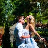 Groom держит невесту на фоне фонтана брызгает стоковое изображение