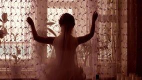 Groom девушки раскрывает занавесы в комнате силуэтом окна акции видеоматериалы