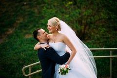 Groom держит невесту на дне свадьбы обнимая Outdoors на na весны Стоковое фото RF