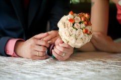 Groom держит руку невест и wedding bouqet стоковая фотография rf