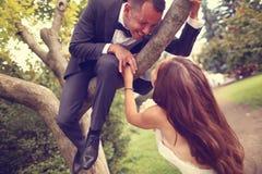 Groom и невеста имея потеху в парке Стоковые Изображения
