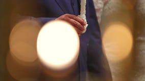 Groom и невеста с свадебной церемонией свечей в церков видеоматериал