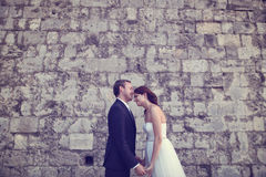 groom и невеста целуя около кирпичной стены Стоковые Изображения RF