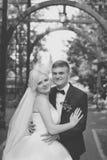 Groom нежно обнимает плеча ` s невесты стоковая фотография