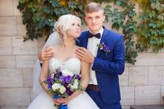 Groom нежно обнимает плеча ` s невесты стоковые фото