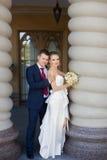 Groom нежно обнял невесту стоя на столбце стоковое изображение rf