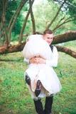 Groom носит его невесту над плечом напольно Стоковое фото RF