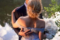 Groom обнимает невесту в романтичном парке водой венчание прогулки стоковое фото rf