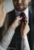 Groom порции невесты одевая для свадебной церемонии Стоковое Изображение RF
