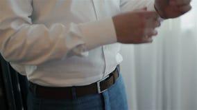 Groom проверяет запонки для манжет на рукаве акции видеоматериалы
