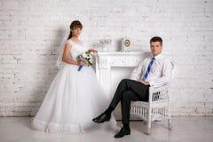 Groom сидит в стуле и невеста стоит около камина Стоковое фото RF