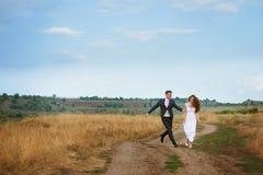 Groom улавливает невесту на поле лета Стоковые Фото