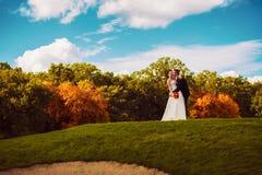 Groom целуя невесту на поле стоковая фотография