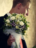 Groom. There is groom with bouquet of white roses. His face turned back stock image