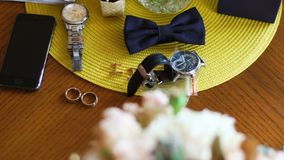 Groom accessories for wedding at the wooden background. Black bow tie, wedding rings, hand watches, phone and studs