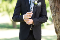 Groom adjusting sleeve in garden. Mid section of groom adjusting sleeve in garden Royalty Free Stock Image