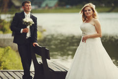 Groom admires a pretty blonde bride standing behind a river Stock Image