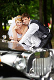 Groom adn bride about retro limousine. Happy groom adn bride about retro limousine stock image