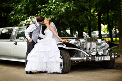 Groom adn bride about retro limousine. Happy groom adn bride about retro limousine royalty free stock photography