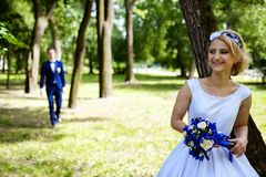 Groom approaches the bride in park Royalty Free Stock Photography