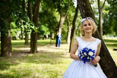 Groom approaches the bride in park Royalty Free Stock Photos