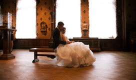 Groom and beautiful bride sitting on bench against window at old castle Royalty Free Stock Images