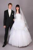 Groom and beautiful bride in studio. Happy young groom and beautiful bride in studio on gray background Stock Photography