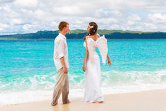 The groom and a beautiful young bride with angel wings on the se Royalty Free Stock Images