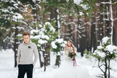 Groom in beige pullover on background of blurred bride in snowy forest. Winter wedding. Artwork. stock photos